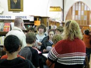 Teacher Mike Quinn (on left) corrals students to explain the scavenger hunt