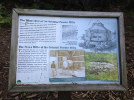 The plaque explaining how the wheel mill was used. Explosions were a common concern when grinding together the components of gunpowder.