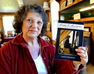 Carol Manchester, holding her book. Portland Press Herald photograph for 9/23/13 article.